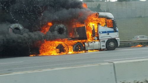 The truck engulfed in flames on the Monash Freeway.