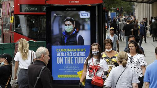 People walk by a COVID-19 infection awareness poster in London, Monday, June 15, 2020