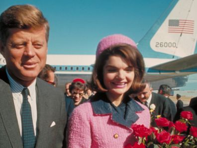 President John F. Kennedy and his wife Jackie, who is holding a bouquet of roses, just after their arrival at the airport for the fateful drive through Dallas.