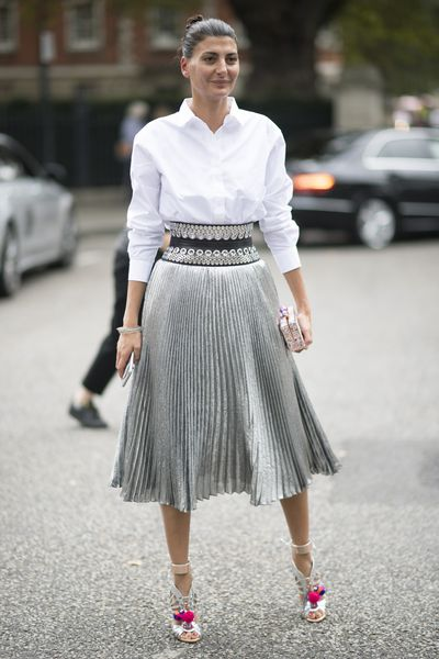 While all eyes were on the models during London Fashion Week most of the exciting sartorial action happens off the runway. Always one to spark a street-style snapping frenzy, Italian fashion editor Giovanna Battaglia cut an elegant figure in between shows, stepping out in this season's metallic midi-skirt coupled with killer accessories. The knife-pleated style staple was perfectly paired with a crisp white shirt, waist-cinching leather belt (Alaia, no less) and head-turning cut-out heels, offering a whimsical touch to the modern look. Simple, classic, chic. <br /> <br /> Key to nailing this look? Balancing a metallic skirt for around-the-clock appeal. Make a metallic skirt daytime appropriate by pairing with versatile shades of white, black or navy, offering a modern yet sophisticated edge. The midi-skirt's effortlessly elegant cut easily passes the office test, and is comfortable enough to breeze through warmer spring days and cooler nights. Style with a simple ponytail and drop earrings for daytime shine. And add a statement red lip, high-shine jewellery and an embellished box clutch post cocktail hour. Most importantly, the heels. Here: the higher and more bling, the better. Statement stilettos – like Battaglia's Sophia Webster's charming pom pom heels – were made to be noticed. A metallic midi-skirt works perfectly as an off-duty option too. Take the look down a notch by swapping out the white shirt for a statement slogan t-shirt in a sporty cut and classic white sneakers– perfect for darting between meetings or making a dash ahead of the coffee queue on weekends. <br /> <br /> Inspired by the super-stylist's masterful fashion week look, we've found the essential pieces you can shop for now. Here's how to dress like a street style star.