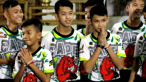 Some of the 12 members of the Wild Boars soccer team greet the media. Picture: EPA/AAP