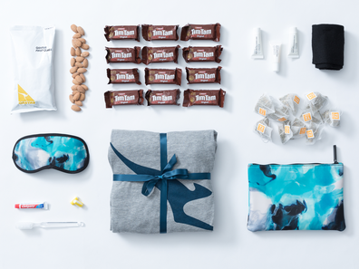 Qantas care package featuring pjamas, amenities and inflight snacks