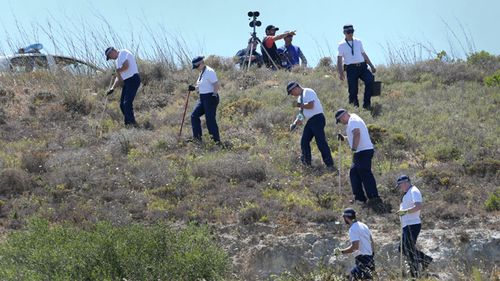 British police officers search an area of wasteland in 2014 during a search for evidence of Madeleine McCann in the town of Praia da Luz, Portugal where she went missing in May 2007.