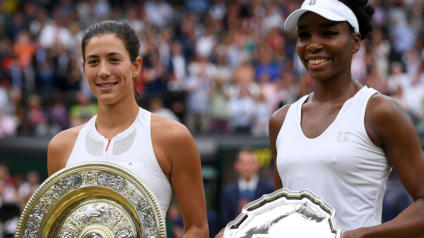 Garbine Muguruza of Spain celebrates victory with the trophy alongside runner up Venus Williams of The United States after the 2017 Wimbledon Ladies Singles final.
