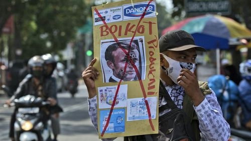 A Muslim man holds a defaced poster of French President Emmanuel Macron during a protest at Al Jihad mosque in Medan, North Sumatra, Indonesia, Friday, Oct. 30, 2020.