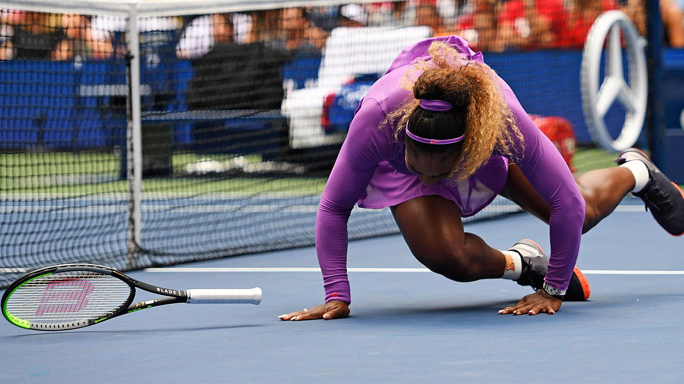 Serena Williams, of the United States, falls while chasing a return to Petra Martic
