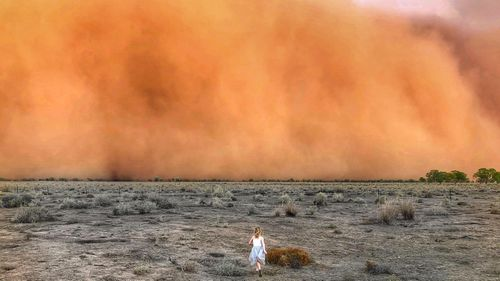 A nine-year-old girl running towards an apocalyptic dust storm in Nyngan, in Central NSW.