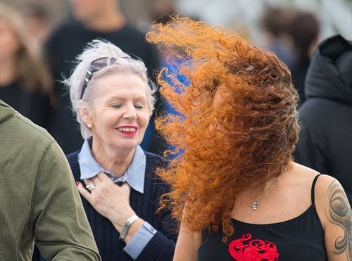 A woman's hair blows into her face as she crosses London Bridge.