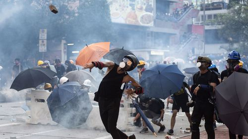 Anti-extradition protesters throw bricks as others react after police fired tear gas at them during clashes in Wong Tai Shin area in Hong Kong.