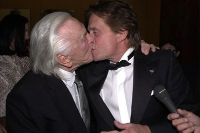 Father and son Kirk Douglas and Michael Douglas shared a celebratory smooch after Michael won a 2001 Humanitarian Award.