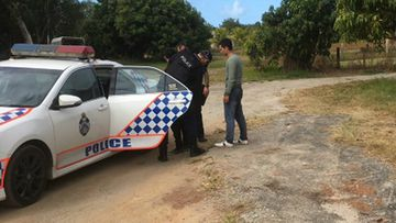 Two suspected asylum seekers being detained by police on the banks of the Daintree River after their fishing vessel sank in waters off the coast of Queensland.