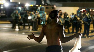 A man stands in front of a line of police in Ferguson. (AP)
