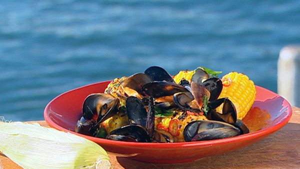 Platter of barbecue mussels and corn with roasted garlic butter
