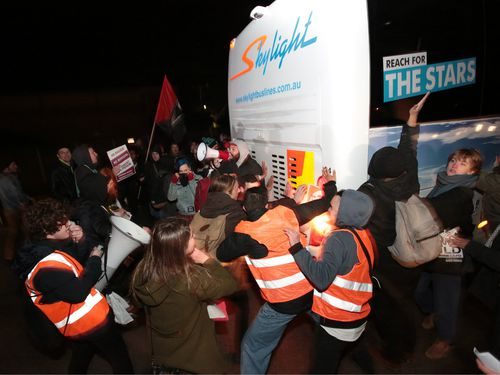 Protesters came close enough to the bus to hit it. (AAP)