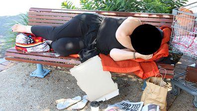 Homeless woman sleeping on seat.