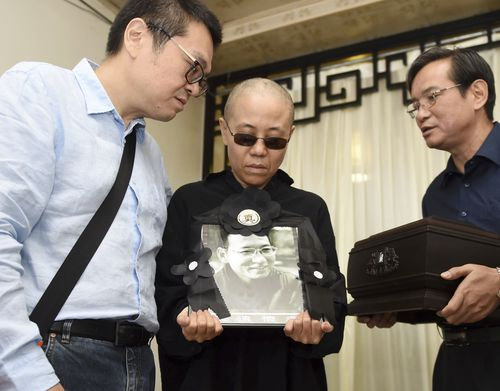 In this July 15, 2017, file photo provided by the Shenyang Municipal Information Office, Liu Xia, center, wife of jailed Nobel Peace Prize winner and Chinese dissident Liu Xiaobo, holds a portrait of him during his funeral in Shenyang in northeastern China's Liaoning Province. A person briefed on the matter said Tuesday, July 10, 2018, that Liu Xia, the widow of Chinese Nobel Peace Prize Laureate Liu Xiaobo, has left China for Europe after eight years under house arrest. (Shenyang Municipal Information Office via AP, File)