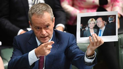 Bill Shorten holds a photograph of Julie Bishop and Chinese businessman Huang Xiangmo.