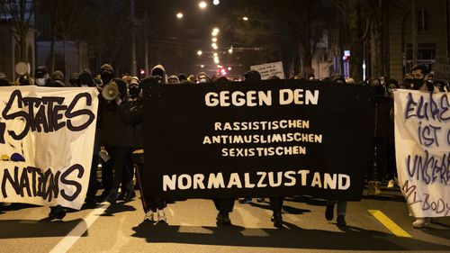 """Demonstrators hold sign reading """"against racist anti-muslim, sexist, normalisation"""" during a protest after the Burqa ban referendum was narrowly approved in Switzerland."""