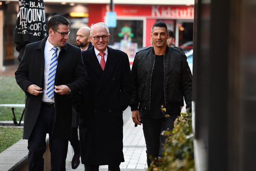 Prime Minister Malcolm Turnbull arrives at a cafe in Manuka, Canberra, this morning with Assistant Minister for Science Zed Seselja. Picture: AAP