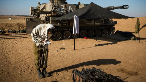 An Israeli soldier prays after helping fire artillery shells into Gaza from Sderot, Israel. The body count in Gaza has reach over 200 people. Picture: Getty Images