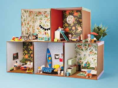 <p>Cardboard apartment block ...</p> <p>1. For each apartment, cut five cardboard squares for the floor and four walls (these ones are 30cm squares).</p> <p>2. Cover each in gift wrap on one side (this is your wallpaper) and trim.</p> <p>3. Use coloured duct tape to tape your floor and five walls together into an open box.</p> <p>4. Stack your apartments together and decorate!</p>