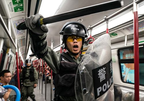 Riot police charge in a train at the Tung Chung MTR station after protesters block the transport routes to the Hong Kong International Airport on September 1, 2019 in Hong Kong, China.