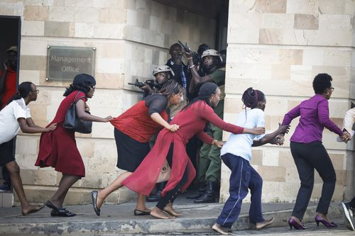 Terrified citizens hold on to each other as they flee to safety in front of armed police.