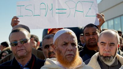 "A Muslim protester holds a placard reading ""Islam equals Peace"" during a demonstration outside Atocha Station in Madrid, Spain. (Getty Images)"