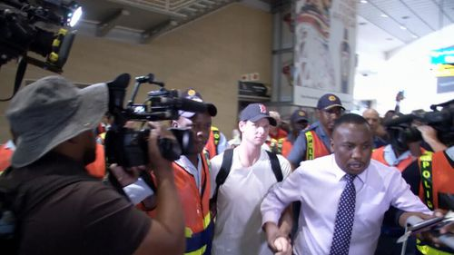 Smith is booed as he is escorted through Johannesburg Airport.