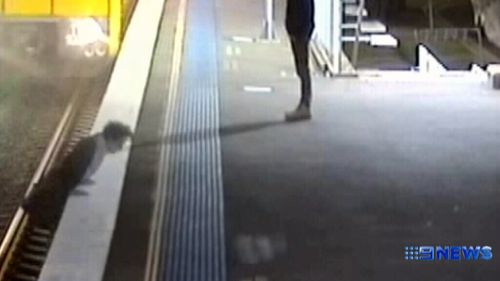 The man narrowly escapes death as an oncoming train just misses hitting him. (9NEWS)