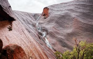 Waterfalls pour down rock face of Uluru during 'magical' weather event