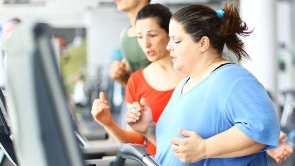Exercising woman running on treadmill