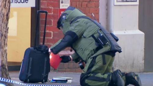 A bomb squad member examines a suspicious bag.