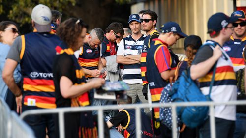 Crows and Cats fans line up to enter the stadium before the Adelaide Crows and Geelong Cats Men's AFL First Preliminary Final at the Adelaide Oval in Adelaide. (AAP)