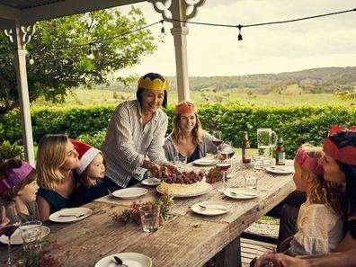 Family eating Christmas lunch on verandah