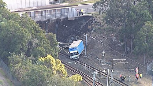 Brisbane delivery truck crashes onto major train line cause heavy delays.