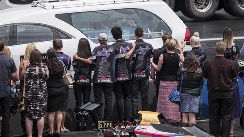 Morners watch the hearse carrying Anita's coffin make a trip down the drag-strip at the Perth Motorplex. (AAP)