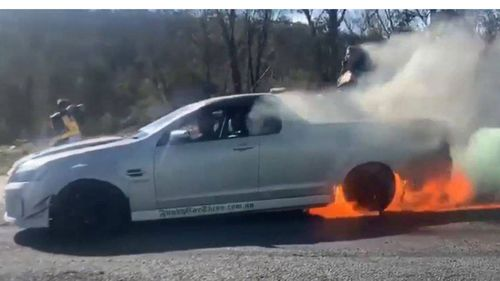 The vehicle's rear tyres erupt into flames as.