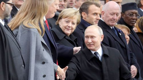 Russian President Vladimir Putin shakes hands with US First Lady Melania Trump as he arrives at the Paris ceremony.