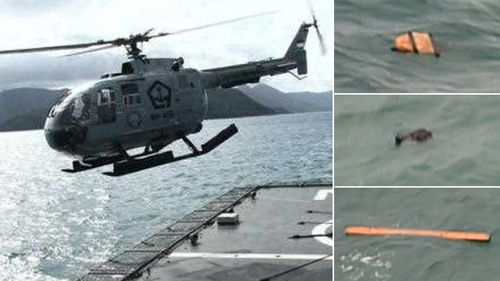 An Indonesian search helicopter and pieces of debris apparently belonging to the AirAsia flight. (AFP)