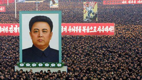 North Koreans hold a massive portrait of Kim Jong-il. (AAP)