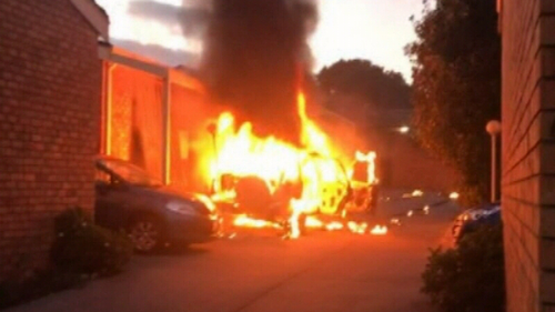A car burst into flames before rolling into a group of units.