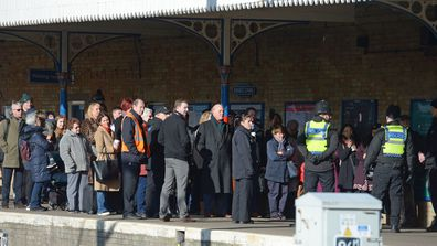 Passengers are held back by police officers as Queen Elizabeth II boards a train at King's Lynn railway station in Norfolk, as she returns to London after spending the Christmas period at Sandringham House in north Norfolk