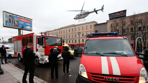 A helicopter flies over the fire trucks after the explosion at Tekhnologichesky Institut subway station. (AAP)