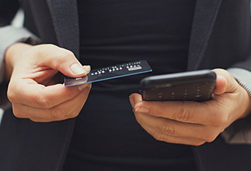 Woman holding bank card and phone (Getty)