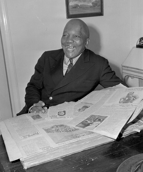 former boxer Jack Johnson sports some gold teeth while looking through a scrapbook of newspaper clippings in Los Angeles. There was no more potent or more closely guarded symbol of white domination at the turn of the 20th Century than the title of heavyweight champion of the world. Then 32-year-old Jack Johnson stepped into the ring. (AP Photo/John T. Burns, File)