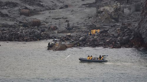 The New Zealand Defence Force recovery team, in yellow suits, enter White Island to recover the bodies.
