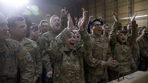 Members of the military cheer as President Donald Trump speaks at a hangar rally at Al Asad Air Base, Iraq.