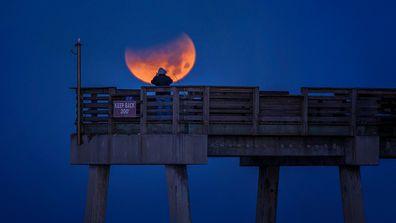 Man taking photo of total lunar eclipse