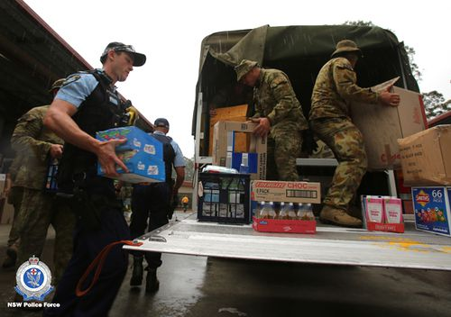 NSW police officers and the ADF unload a truck of supplies.